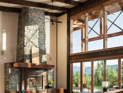Dark timber beams flow through to the exterior above while a large stone fireplace and window-wall add character and space to the rest of the room