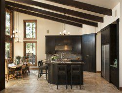 Dark wood cabinetry matches the angled timber in this kitchen