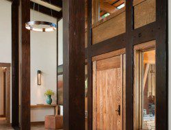 The length of this Washington home's interior entry is framed in dark posts and beams