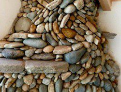 This river rock fireplace looks like it is made using the principles of a dry stone wall and with all that stone it would radiate heat long after the fire goes out.