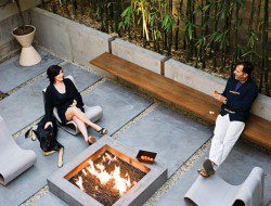 Courtyard with custom made fire pit, concrete pavers, and bench.