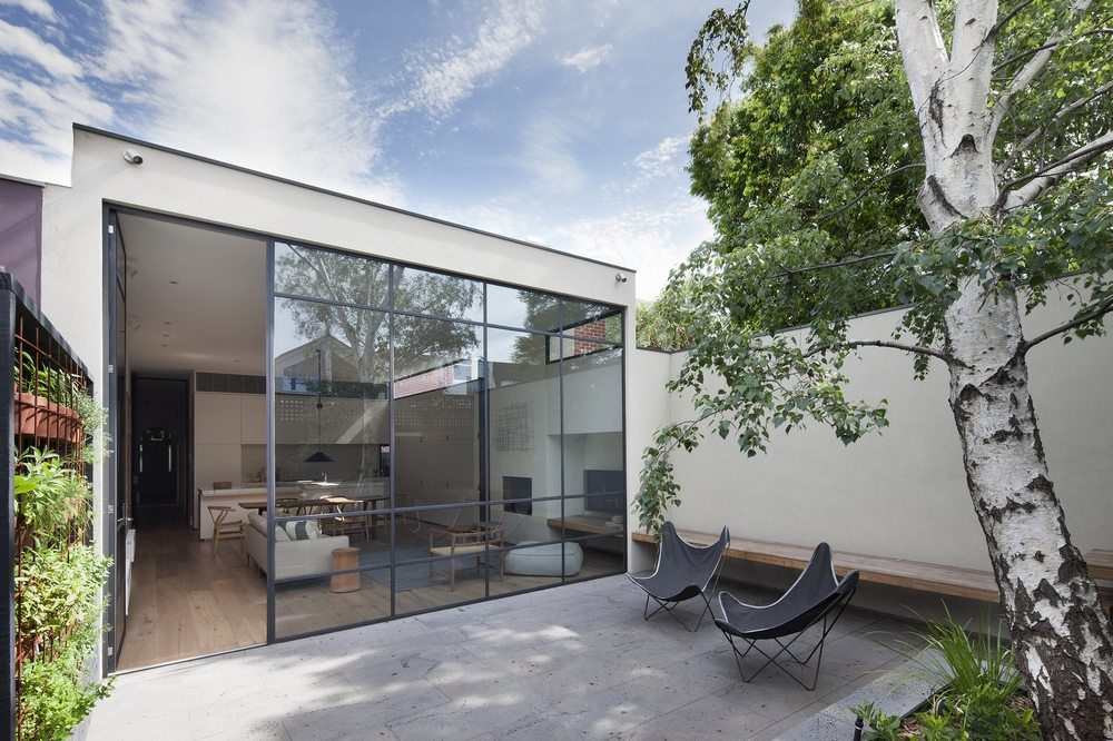 Large glass windows bring the outdoors in while bathing the home with sunlight.