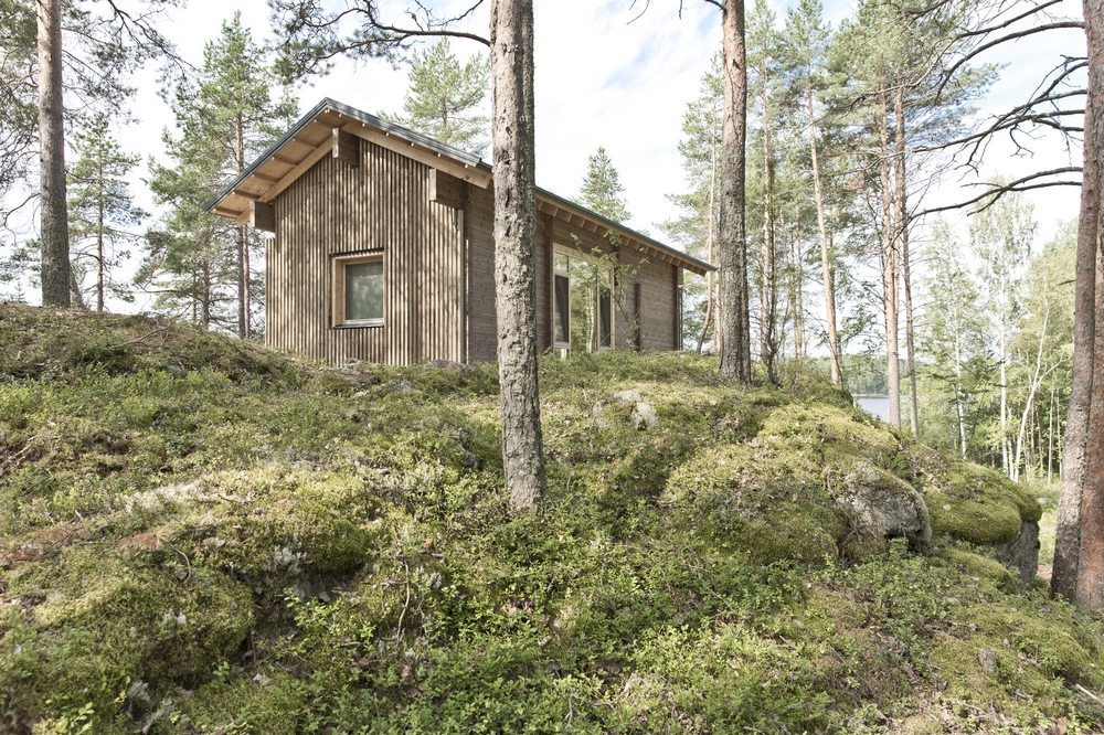 The cabin sits on top of a narrow granite ridge, surrounded by tall trees with stunning lake views.