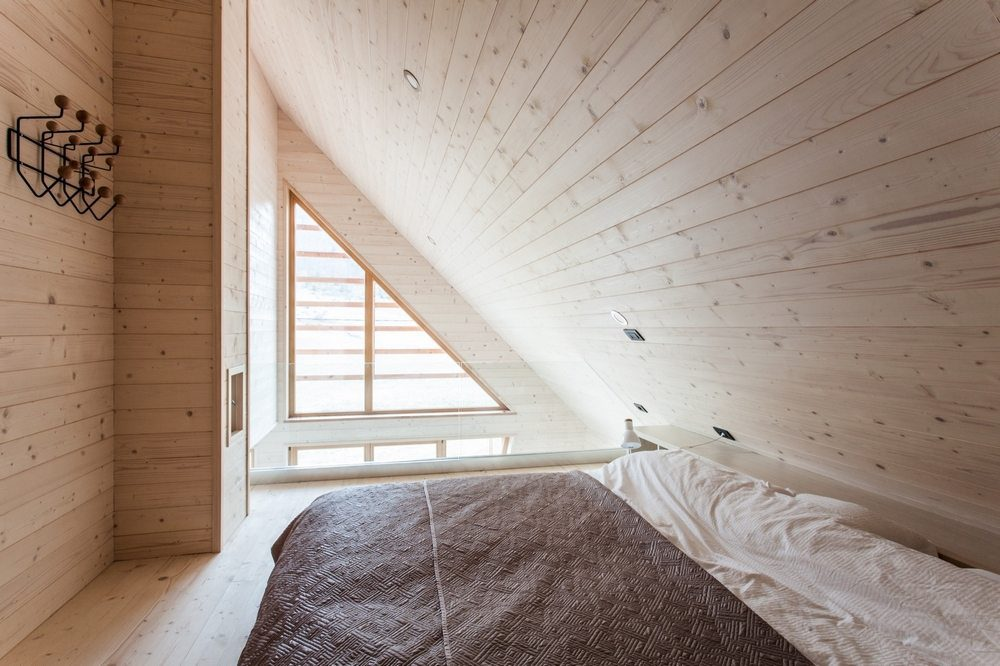 The bedroom walls follow the slanted shape of the roof.