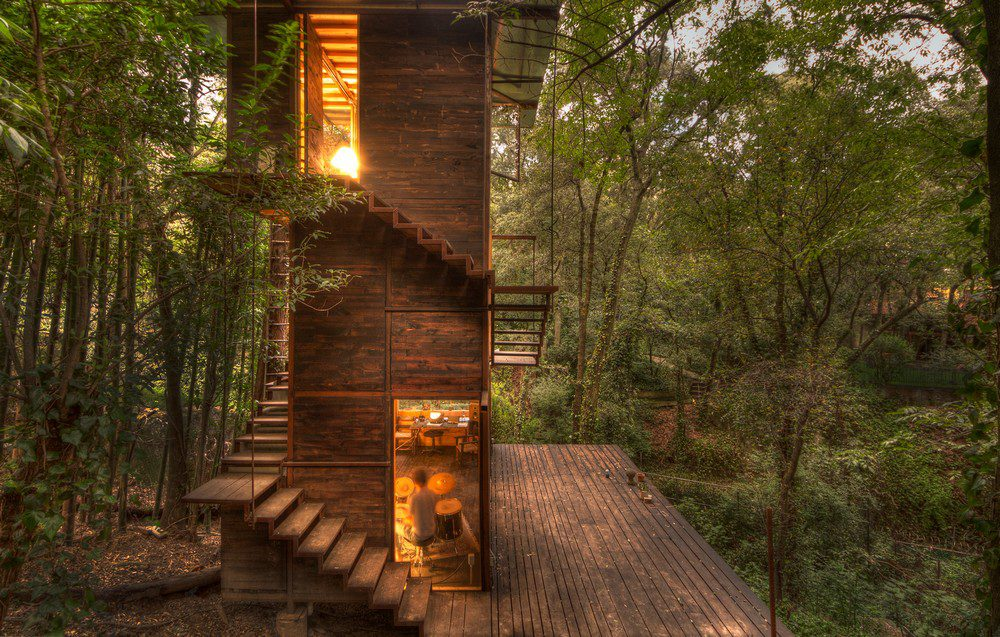 The fully illuminated Casa Flotante looks like a beacon in the midst of the forest.